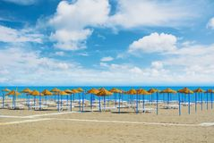 Empty perfect dreamy paradise beach with umbrellas tents made of. Palm leaves and white beach lounge chairs standing at the sandy bay by the blue sea and Stock Images