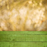 Empty perspective green wood over blurred trees with bokeh background, for product display montage Stock Image