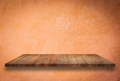 Empty perspective top wooden shelf on orange wall Royalty Free Stock Photos