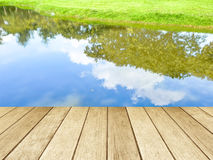 Empty perspective wood over trees and blue sky reflection. Background Royalty Free Stock Photography