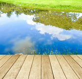 Empty perspective wood over trees and blue sky reflection. Background Royalty Free Stock Photos
