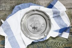 Pewter plate with bitcoin simbol. Empty pewter plate with bitcoin simbol and checkered kitchen towel on a rough wooden table, top view Royalty Free Stock Photography