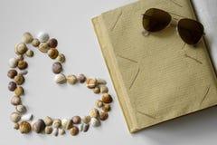 Empty photo album, sunglasses and seashells heart. stock photos