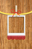 Empty photo frame with clothespin over wooden. Background Stock Image