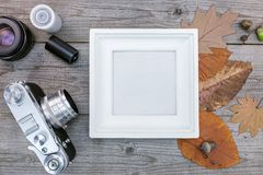 Empty photo frame, old camera and negative films on wooden backg. Round with dried leaves Royalty Free Stock Photography