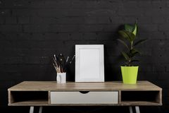 Empty photo frame, paintbrushes and plant in flowerpot. On wooden table stock image