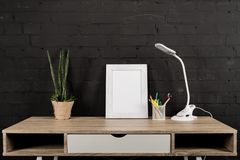 Empty photo frame, plant in flowerpot, office supplies and table lamp. At workplace stock image