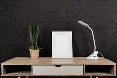 Empty photo frame, plant in flowerpot and table lamp. At workplace royalty free stock photography