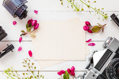 Empty photo frame, retro camera, photo film rolls and flowers Royalty Free Stock Photos