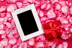 Empty photo frame with  sweet pink roses  petal and red gift box Royalty Free Stock Photography