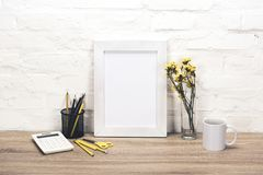 Empty photo frame on table. Close up view of empty photo frame, office supplies, coffee cup and flowers in vase on table royalty free stock photography