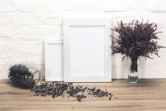 Empty photo frames and flowers on table. Close up view of empty photo frames and lavender flowers on wooden table royalty free stock photo