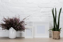 Empty photo frames and flowers on tabletop. Close up view of empty photo frames and flowers on wooden tabletop royalty free stock photos
