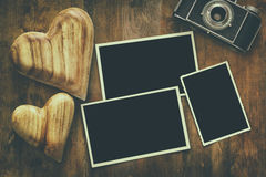 empty photo frames next to old camera and hearts Stock Photography