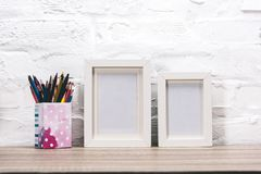 Empty photo frames and pencils. Close up view of empty photo frames and pencils on wooden surface royalty free stock photos