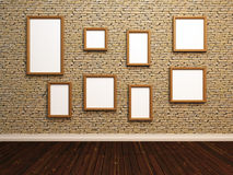 Empty photo frames on stone tile wall. Royalty Free Stock Photography