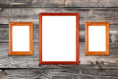 Empty photo frames on wooden wall. Three empty photo frames on old wooden wall Royalty Free Stock Photos
