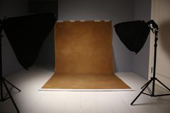 Empty photo studio with lighting equipment. Gray and brwon background stock photography