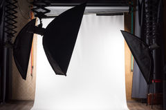 Empty photo studio with lighting equipment and white paper background ready for photoshoot. Royalty Free Stock Images