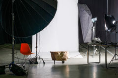 Empty photo studio with modern interior and lighting equipment. Preparation for studio shooting: empty chair and studio lighting. Royalty Free Stock Images