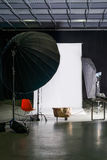 Empty photo studio with modern interior and lighting equipment. Preparation for studio shooting: empty chair and studio lighting. Stock Images