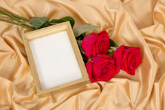 Empty photoframe with a bouquet of red roses Stock Images