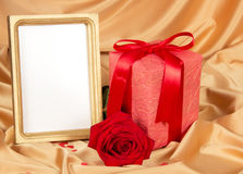 Empty photoframe with rose and gift Royalty Free Stock Images