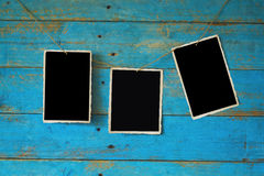 Empty photos for your pix. Empty photo frames hanging on old blue grungy wooden planks background Stock Image
