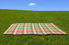 An empty picnic blanket on green grass. Under blue sky with one cloud. Family holiday concept. copy space Stock Images