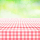 Empty picnic gingham tablecloth, green background. Empty picnic table, covered with checkered gingham tablecloth. Blurred green background. Summer picnic Stock Image
