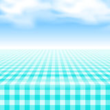 Empty picnic table, covered checkered tablecloth. Empty picnic table, covered with checkered gingham tablecloth. Clear blue sky background. Summer picnic Royalty Free Stock Image