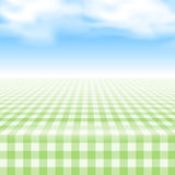 Empty picnic table, covered checkered tablecloth. Empty picnic table, covered with checkered gingham tablecloth. Clear blue sky background. Summer picnic Royalty Free Stock Photo