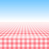 Empty picnic table, covered checkered tablecloth. Empty picnic table, covered with checkered gingham tablecloth. Clear blue sky background. Summer picnic Stock Photos