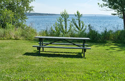 Empty picnic table with Penobscot Bay in the background. An empty picnic table on green grass with brush and Penobscot Bay in the background at Belfast Maine in Royalty Free Stock Photos
