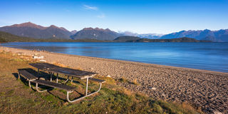 Empty picnic table at a shore of a lake Stock Photos