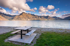 Empty picnic table by the shore of Lake Wakatipu, New Zealand at Daylight Stock Photo