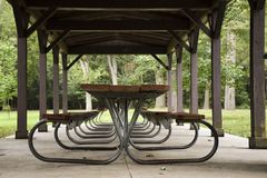 EMPTY PICNIC TABLES UNDER PAVILION. Several picnic tables in a line under a pavilion structure are protected from the weather stock photo
