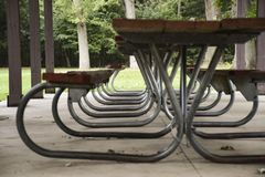 EMPTY PICNIC TABLES UNDER PAVILION. Several picnic tables in a line under a pavilion structure are protected from the weather royalty free stock photography