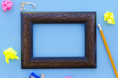 Empty picture frame on a blue background with writing equipment Stock Image