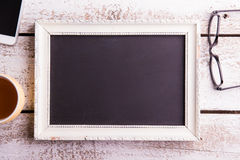 Empty picture frame, eyeglasses, cup of coffee and smartphone Royalty Free Stock Images