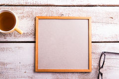Empty picture frame, eyeglasses and cup of tea Stock Photography
