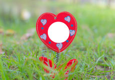 Empty of picture frame heart shapes on green grass Stock Photos