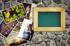 Empty picture frame with a pile of photographs Stock Photos