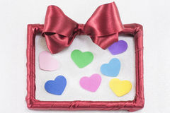 Empty picture frame with red ribbon with colorful hearts Stock Images