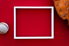 Empty picture frame on a red wall with baseball equipment Royalty Free Stock Image