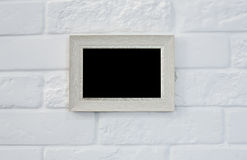 Empty picture frame at white brick wall Royalty Free Stock Images