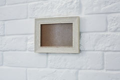 Empty picture frame at white brick wall Stock Photo