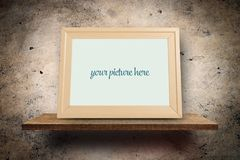 Empty picture frame on wooden shelf on grungy wall royalty free stock photography