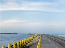 Empty pier. A port entrance, empty, two piers, beacons. Two small figures in the far distance Stock Photo