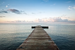 Empty pier. Empty wooden pier in the morning with beautiful clouds and azure sky Stock Image